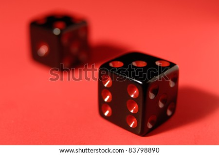 Pair of black dice isolated on red background