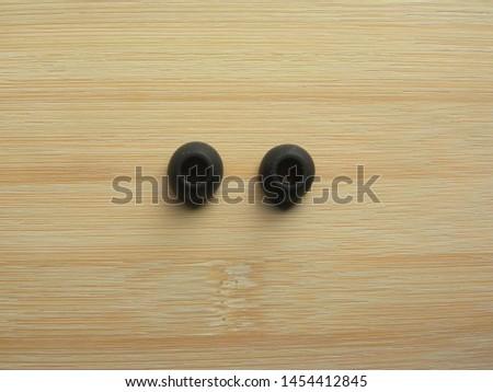 Pair of black earphone pads of in-ear earphones kept on wooden table