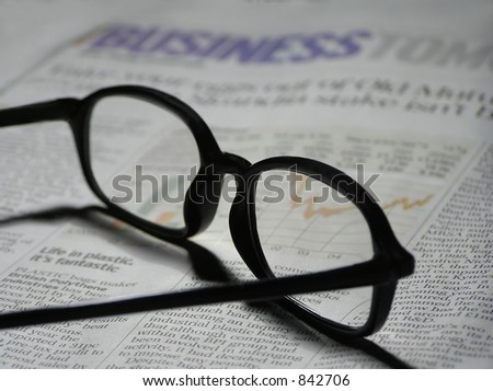Pair of black glasses laying on a newspaper with financial information