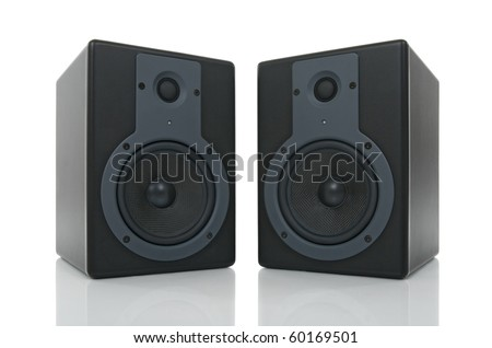 Pair of black loud speakers with reflection on white background.