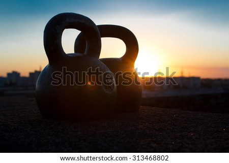 Pair of black one-pound kettlebells at sunset background over the city. Concept of access for health improvement and physical development in free time after busy day