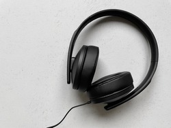 pair of black over-ear headphones on off-white background with copy space