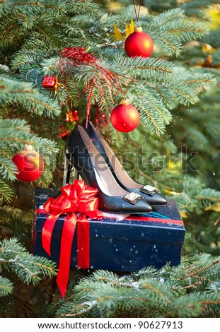 Pair of black women shoes against Christmas tree