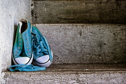 pair of blue and green sneakers on gray cement stairs