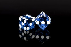 Pair of blue casino gaming/gambling dice isolated on a black background with reflection.