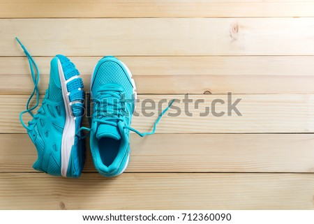 pair of blue sneakers on wooden background. #712360090