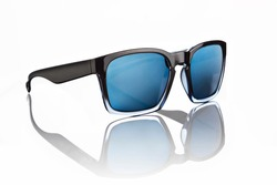 Pair of blue tinted sunglasses with black frames on white background, with reflection.