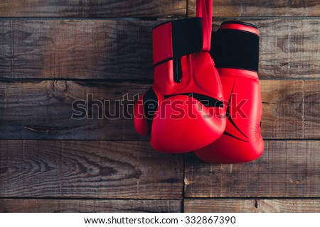 Pair of boxing gloves hanging in a rustic wooden wall. Vintage tone.