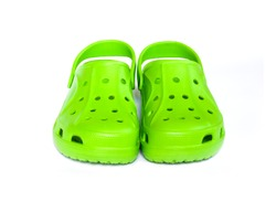 Pair of bright green clogs isolated on white background. Front view