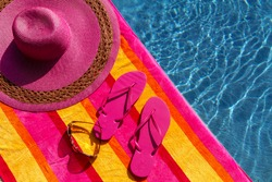 Pair of bright pink flip flops by the pool on a bright orange, pink, red and yellow striped towel with sunglasses and big pink floppy hat