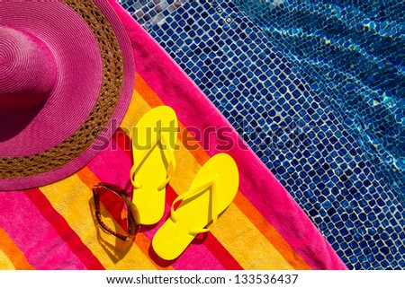 Pair of bright yellow flip flops by the pool on a bright orange, pink, red and yellow striped towel with sunglasses and big pink floppy hat