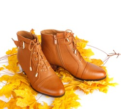 Pair of brown female boots with bright autumn leaves isolated on white background