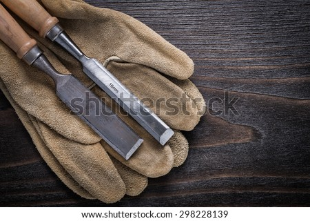 Pair of brown leather gloves with firmer chisels on vintage wooden board top view image construction concept.