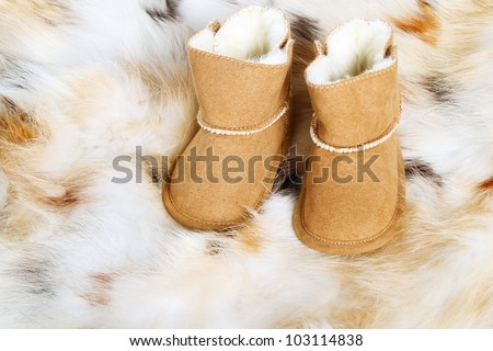 Pair of brown winter boots on fox fur background