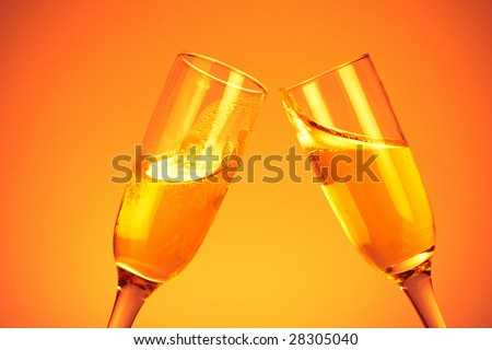 Pair of champagne flutes on orange background