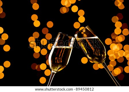Pair of champagne flutes toasting on a black background with out of focus yellow and orange lights. Studio Shot. - stock photo