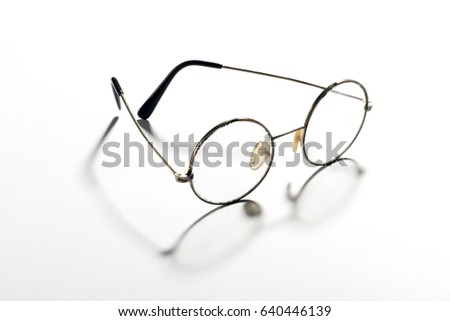 Pair of classic round vintage eyeglasses, glasses or spectacles with a thin wire frame displayed open throwing a shadow on a white reflective background #640446139