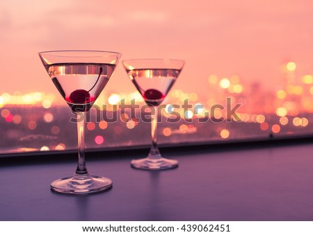 Pair of cocktail glasses in a colorful night setting.
