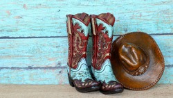 pair of colorful blue and red cowboy boots and hat standing on natural wood with a blue wooden background