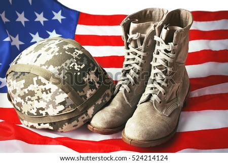 Pair of combat boots, military helmet and USA flag, close up view