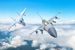 Pair of combat fighter jet on a military mission with weapons - rockets, bombs, weapons on wings flies high in the sky above the clouds
