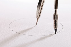 pair of compasses drawing circle on a paper