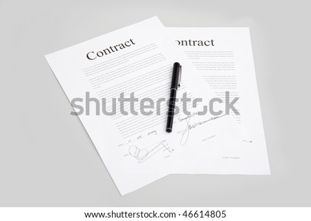 Pair of contracts containing generic text and fictitious signatures with a pen on the gray surface of a desk