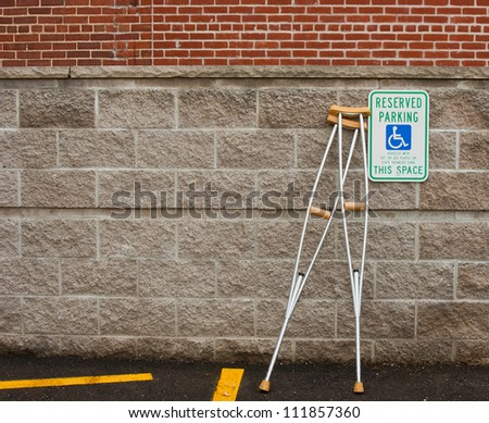 pair of crutches leaning next to a handicapped parking sign