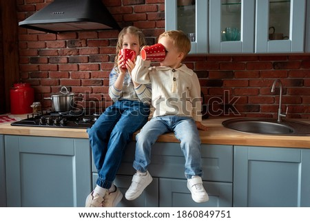 Pair of cute adorable caucasian blond siblings boy and girl enjoy have fun sitting on kitchen counter and drinking hot tea or chocolate from big red mug. Happy family kid and healthy lifestyle stock photo