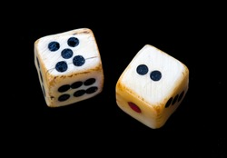 Pair of dice made of bone or ivory. Vintage or antique. Closeup isolated against black background.