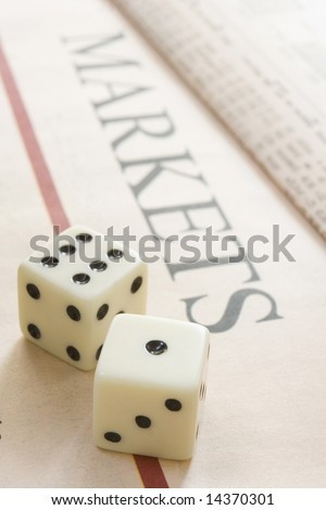 pair of dice resting on a paper with the headline Markets