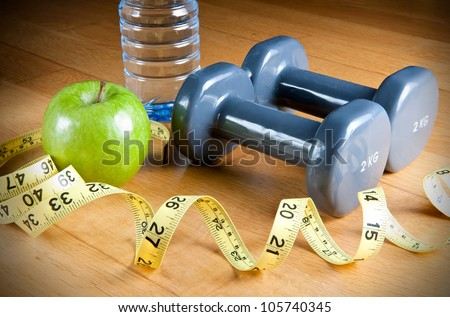 Pair of dumbbells, green apple, measuring tape and bottle of water. Exercise and healthy diet concept.