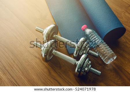 Pair of dumbbells with blue yoga mat on wood floor,flare light #524071978
