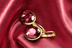 Pair of elegant ruby gold earrings on red satin background