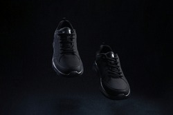 Pair of fashion black unbranded sneakers flying on dark background. Black sport running shoes levitate in air.