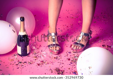 Pair of feet at a new years eve countdown party with confetti, champagne and balloons on the floor #352969730