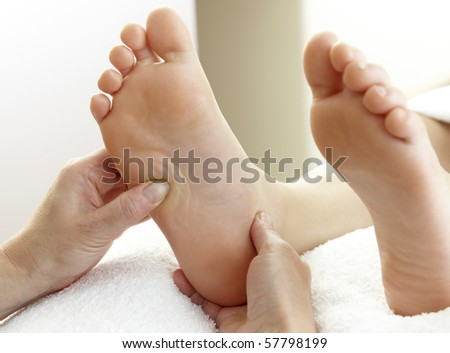 pair of feet being massaged by hands on white towel