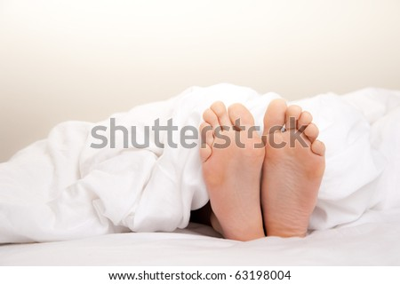 Pair of Feet in Bed on White Sheets