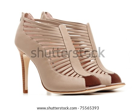 Pair of female beige shoes over white background