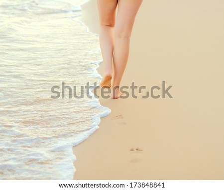 Pair of female legs on a seashore. #173848841
