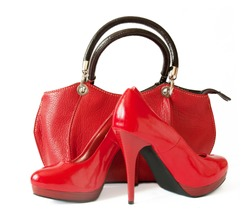 Pair of female red shoes and handbag over white