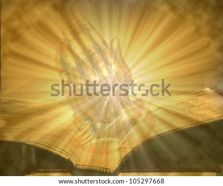 Pair of folded hands praying on golden lighted open bible