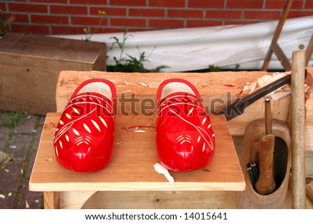 Pair of freshly made red Dutch wooden shoes with the tools that made them
