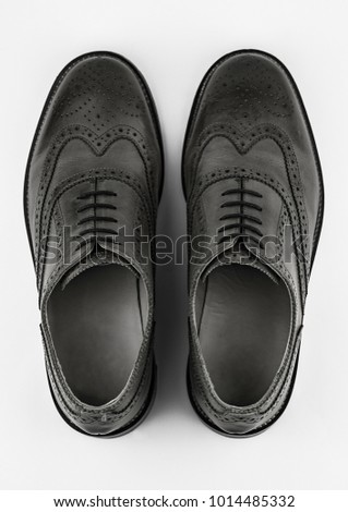 Pair of generic black brogue shoes shot from above on a white background. #1014485332