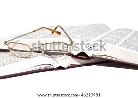 Pair of glasses on an open books isolated on white