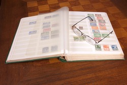 Pair of glasses sitting on a philatelic stamp collection album