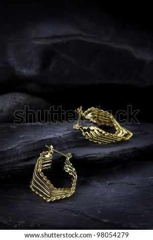 Pair of golden earrings placed on black stone