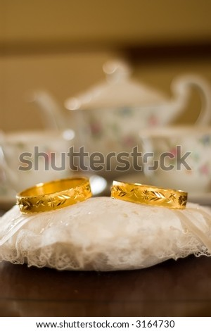 stock photo Pair of golden wedding rings sitting on pillow for Chinese