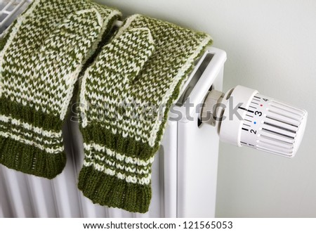 Pair of green knitted gloves drying on the radiator with thermostat
