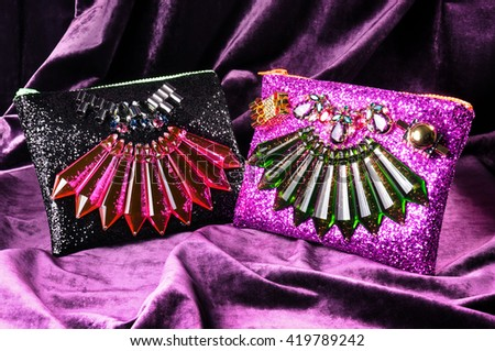 Pair of hand bags for female (black & violet) isolated on violet texture. Beautiful jewelry elements. #419789242